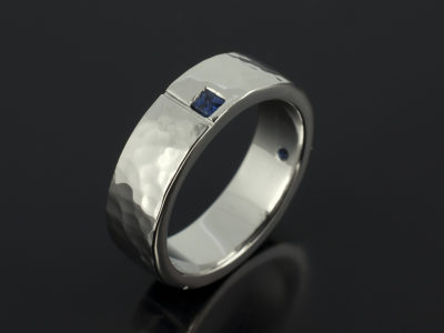 Gents Platinum Hammered Finish Secret Set Princess Cut Sapphire Engagement Ring with Grooved Detail.