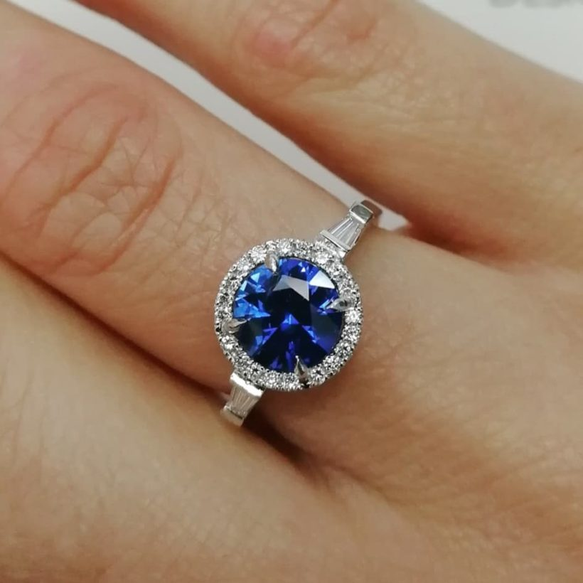 round brilliant cut sapphire and diamond ring, diamond halo ring with sapphire centre stone, diamond halo and tapered baguette side stones, classic style sapphire and diamond engagement ring