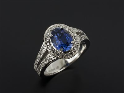 Oval Cut Blue Sapphire 1.41ct Claw Set In Platinum With a Pavé Set Round Brilliant Cut Diamond Halo and Split Shoulder 0.45ct (64) F Colour Vs Clarity Minimum