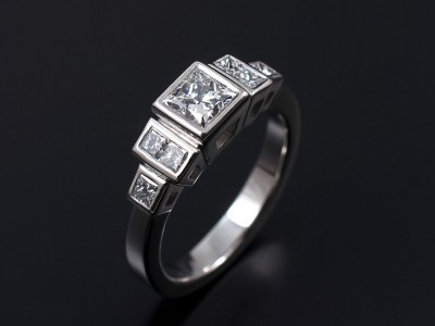 Platinum Rub Over Stepped Engagement Ring with a 0.54ct E VS1 and 6 x 0.10ct F VS Princess Cut Diamonds.