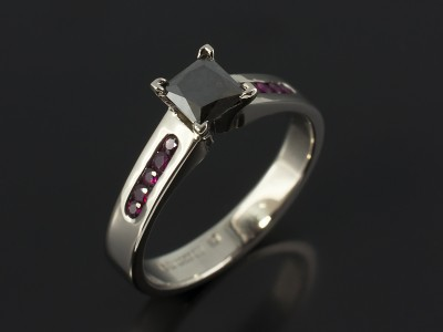 Princess Cut Black Diamond 0.67ct with Channel Set Round Rubies 0.18ct in a Contemporary Palladium Design.