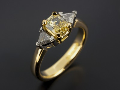 Radiant Cut 0.76ct Fancy Yellow Diamond with Trilliant Cut Diamonds in a Palladium and 18kt Yellow Gold Trilogy Setting.