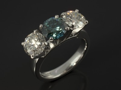 Round Brilliant Cut 1.50ct Blue Diamond with Round Brilliant Cut Side Diamonds 1.16ct and 1.33ct H Colour SI Clarity in an 18kt White Gold Claw Set Trilogy Setting.