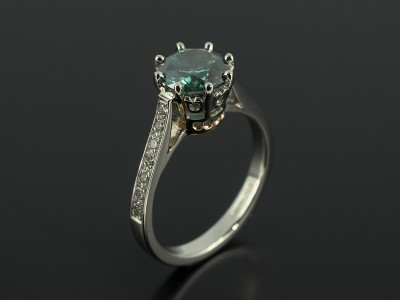 Round Brilliant 1.52ct Green Blue Diamond with Pavé Set Diamond Shoulders in a Platinum and Rose Gold Claw Set Design.
