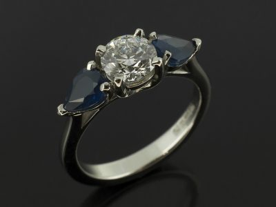 Round Brilliant 0.62ct D Colour SI1 Clarity EXEXEX with 0.90ct Pear Cut Sapphires in a Palladium Trilogy Design.