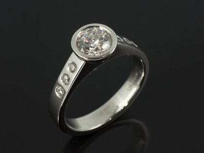 Round Briliant 0.76ct E Colour SI1 Clarity EXEXEX in a Platinum Rub Over Setting with Secret Set Diamond Shoulders.