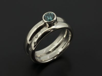 Round Brilliant Cut Blue Diamond 0.30ct in a Palladium Rub Over Set Design with Fitted Secret Set Diamond Wedding Ring.
