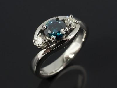 Round Blue Diamond 0.77ct with 2 x 0.14ct Round Brilliant Diamonds in a Palladium 4 Claw Twist Band Design.