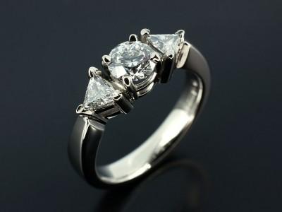 Round Brilliant 0.51ct E Colour SI1 Clarity with 0.23ct Total Trilliant Cut Diamonds in a Palladium Trilogy Setting.