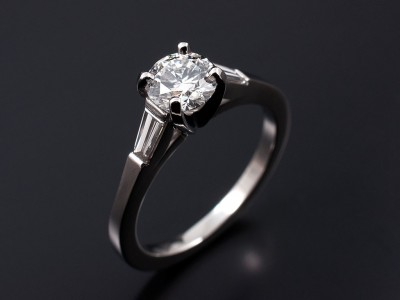 Round Brilliant 0.61ct G SI1 with 0.22ct (2) F VS Tapered Baguettes in a Platinum 4 Claw Setting.