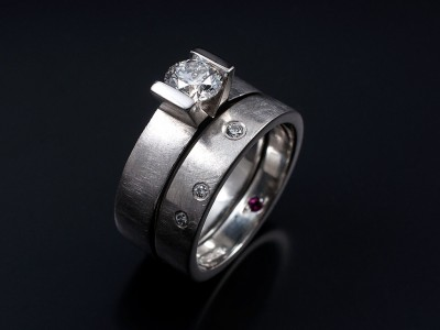Round Brilliant 0.62ct G SI1 Platinum Tension Set Engagement Ring with Matching Wedding Ring with Secret Set Diamonds and Ruby.