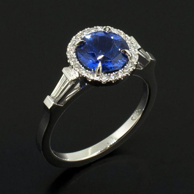 Round Brilliant Cut Sapphire 1.49ct with Tapered Baguette Cut Diamonds 0.20ct Total and Round Brilliant Cut Diamonds in a Platinum Halo Design Ladies Ring