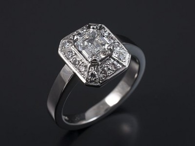 Emerald Cut 0.92ct E VS2 in an 18kt White Gold Halo Setting with Pave Set Round Brilliant Diamonds.