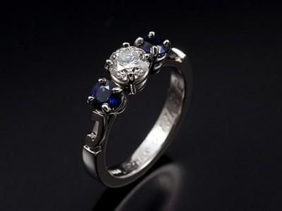 Platinum Trilogy Ring with Round Brilliant Diamond 0.46ct F Colour VS Clarity Minimum and 2 x Round Sapphires 0.57ct total. Letters 'J' and 'R' located on each shoulder
