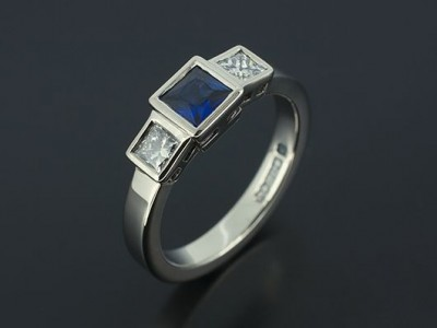Palladium Trilogy Engagement Ring with Princess Cut Sapphire 0.46ct and Princess Cut Diamonds 0.37ct (2) F Colour VS Clarity Min Set in Rub Over Settings.