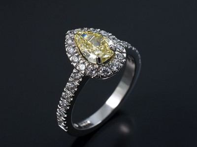 Fancy Intense Yellow 0.74ct VS1 Clarity Pear Cut Diamond in a Platinum Diamond Claw Set Halo Design.