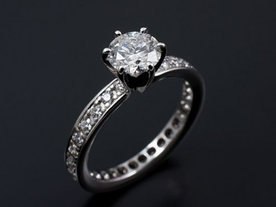 Round Brilliant 1.09ct E SI1 in a 6 Claw 18kt White Gold Setting with Pave Set Band.