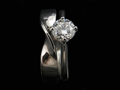 Platinum NSEW Engagement Ring with a 0.52ct F VS2 Round Brilliant Diamond with an Integrated Twisted Wedding Ring.