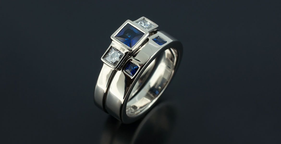 Princess Cut Sapphire 0.46ct with Princess Cut Diamonds 0.37ct Total with Fitted Wedding Ring with 2 x Princess Cut Sapphires 0.15ct in a Palladium Rub Over Contemporary Design.