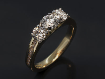 Round Brilliant Cut Diamond Trilogy ring in Yellow Gold with Round Diamond Shoulders