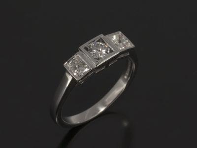 18kt White Gold Rub-over Set Design. Round Brilliant Cut Diamond, 0,25ct with Square Cut Diamond Sides, 0.45ct (2)