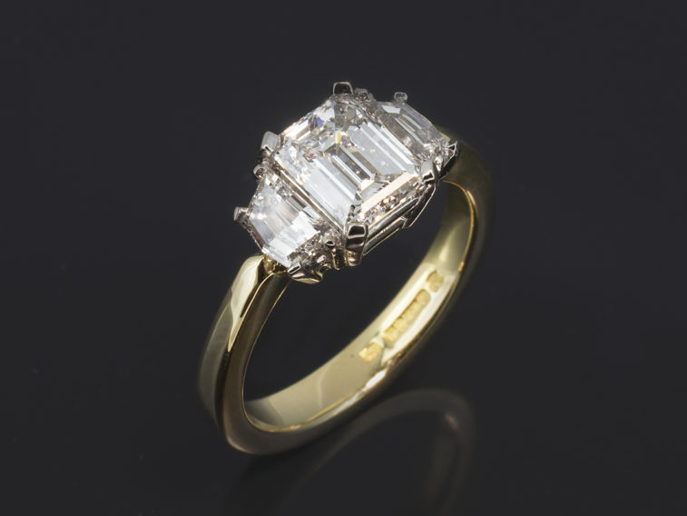 Emerald cut diamond engagement ring, 18kt yellow gold claw set trilogy with 1.00ct centre stone