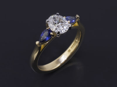 18kt Yellow Gold and Platinum Trilogy Ring. Oval Cut Diamond, 0.71ct, D Colour, SI1 Clarity. Very Good Polish, Excellent Symmetry. Pear Shape Sapphires, 5X3mm.
