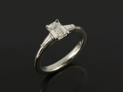 Emerald Cut Diamond 0.63ct E Colour VS2 Clarity with Tapered Baguettes 0.25ct F Colour VS Min in a Platinum Claw Set Trilogy Design
