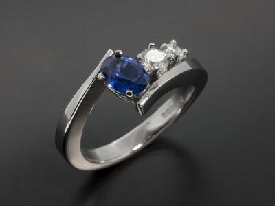 Oval Cut 1.09ct Sapphire and Round Brilliant Cut 0.27ct & 0.15ct Platinum Claw Set Twist