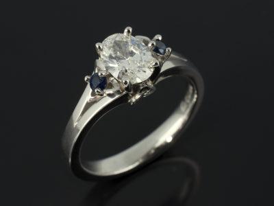 Oval Cut Diamond 0.71ct F Colour SI2 Platinum Design with Round Brilliant Cut Sapphires Triquetral