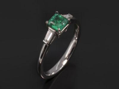 Platinum Claw Set Design. Asscher Cut Emerald, 0.47ct. Tapered Baguette Cut Diamonds, 0.21ct (2), F Colour, VS Clarity