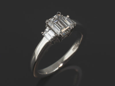 Platinum Claw Set Trilogy Design Emerald Cut Diamond, 1.00ct, E Colour, VS2 Clarity. Trapezium Cut Diamonds, 0.43ct (2). F Colour, VS Clarity Minimum