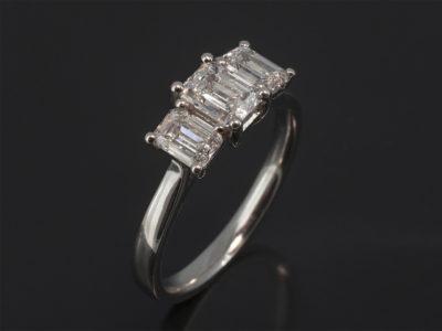 Platinum Claw Set Trilogy Design. Emerald Cut Diamond, 0.63ct, F Colour, VS Clarity. Emerald Cut Diamonds, 0.86ct (2), F Colour, VS Clarity