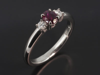 Platinum Claw Set Trilogy Design. Oval Cut Ruby, 0.34ct. Round Brilliant Cut Diamonds, 0.10ct (2). F-G Colour, SI Clarity