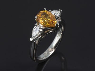 Platinum Claw Set Trilogy Design. Pear Shape Yellow Sapphire, 2.78ct. Pear Shape Diamonds, 0.60ct (2), F Colour VS Clarity Minimum