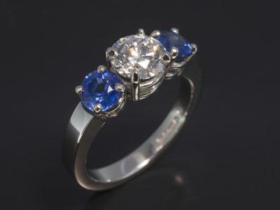 Platinum Claw Set Trilogy Design. Round Brilliant Cut Diamond, 1.12ct, E Colour, SI1 Clarity. Round Blue Sapphires, 5mm x 2