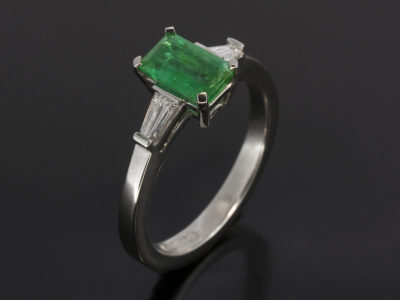 Platinum Claw Set Trilogy. Emerald Cut Emerald, 0.78ct. Tapered Baguette Cut Diamonds, 0.23ct (2) FSI MIN
