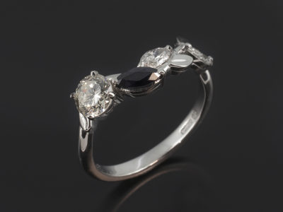 Platinum Claw Set Vine Design Wedding Ring. Round Brilliant Cut Diamond, 0.38ct Marquise Cut Blue Sapphire, 0.24ct, Marquise Cut Diamonds, 0.20ct (2), F Colour, SI Quality.