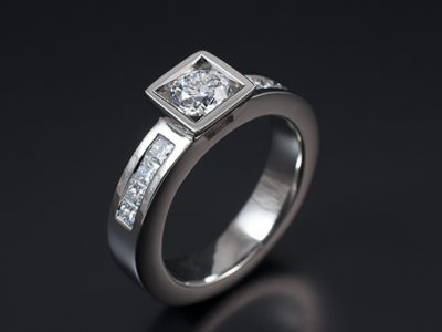 Round Brilliant 0.50ct E Colour SI1 Clarity with 8 x Princess Cut Diamonds Channel Set into Shoulders in a 18kt White Gold Contemporary Square Rub Over Setting.