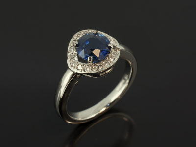 Round Sapphire 1.61ct and Round Brilliant Cut Diamond 0.08ct Total in a Platinum Claw and Pavé Set Halo Design