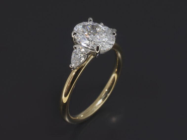 Platinum & 18kt Yellow Gold Claw Set Trilogy Design. Oval Cut Diamond, 1.20ct. E Colour, VVS2 Clarity. Pear Cut Diamonds, 0.21ct (2). F Colour, VS Clarity Minimum