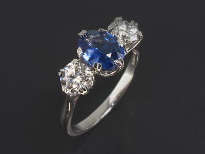 Platinum Claw Set Trilogy Design. Oval Cut Blue Sapphire, 1.74ct. Round Brilliant Cut Diamonds, 0.61ct, D Colour SI Clarity, Excellent Cut, Polish and Symmetry. 060ct, D Colour, SI1 Clarity, Excellent Cut, Polish and Symmetry.
