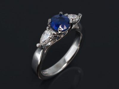 18kt White Gold Trilogy Design. Round Blue Sapphire, 1.25ct. Pear Cut Diamonds, 0.62ct (2), F Colour, SI Clarity.