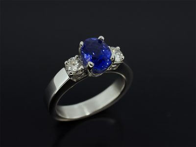 Oval Cut Blue Sapphire 1.71ct with round brilliant cut diamonds 0.40ct (2) Set in platinum in a trilogy design