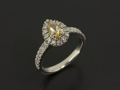 Pear Cut Fancy Yellow Diamond 0.60ct with Claw Set Diamond Halo and Shoulders 0.39ct Total in a Platinum Design