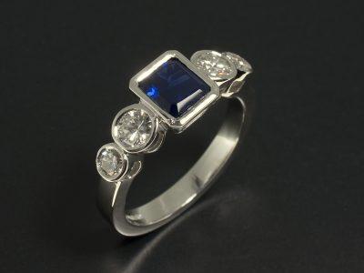 Platinum 5 Stone Rub Over Set Design with Emerald Cut Sapphire 1.19ct with Round Brilliant Cut Diamonds 0.76ct Total