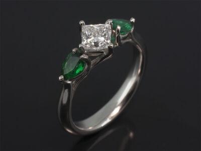 Platinum Claw Set Trilogy Design. Princess Cut Diamond, 0.62ct, E Colour, VS1 Clarity. Pear Shape Emeralds, 0.44ct (2)