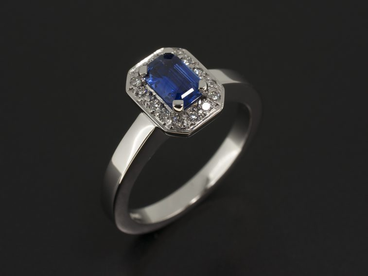 Platinum Halo Design with Emerald Cut Sapphire 0.50ct and Round Brilliant Cut Diamonds Pavé set into Halo