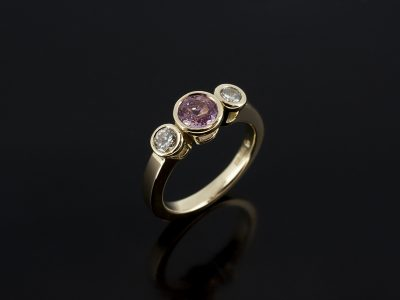 18kt Yellow Gold Trilogy Ring with Pink Peach Sapphire 5.5mm Centre Stone Rubover set