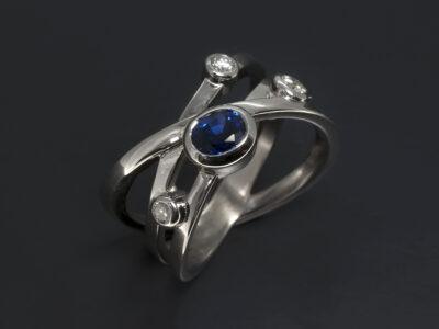 9kt White Gold, Diamond and Sapphire Crossover Design. Oval Sapphire 0.88ct. Round Brilliant Cut Diamonds, 0.30ct (3). F Colour, VS Clarity Minimum